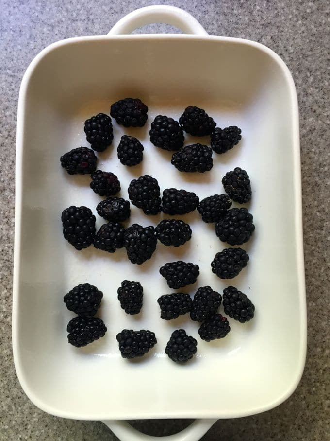 Fresh blackberries spread in the bottom of a white baking dish for Simple Lemon Blackberry Bread Pudding
