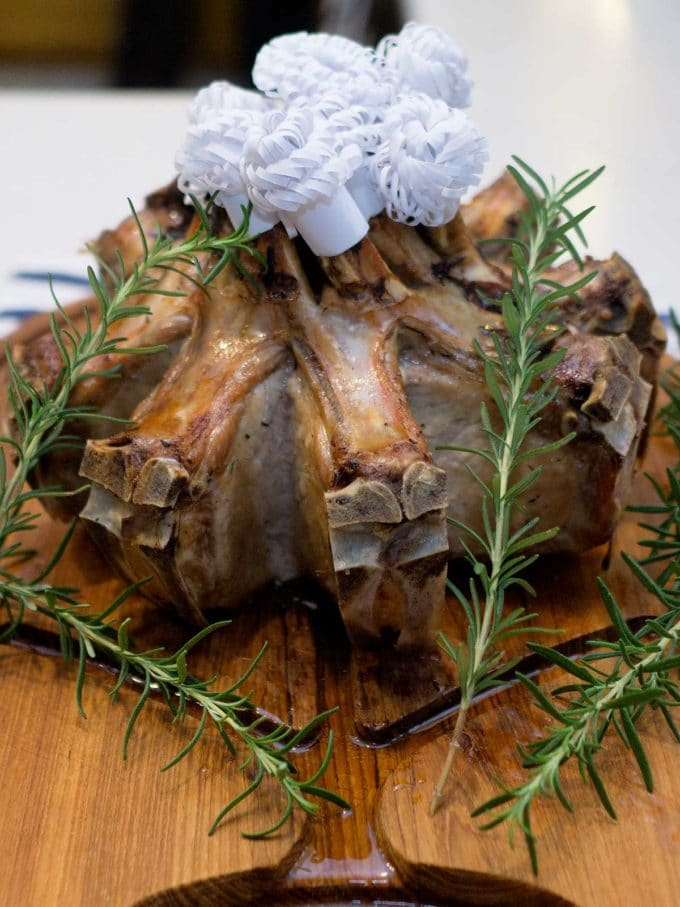 A whole Crown Roast of Pork with Rosemary on a cutting board.