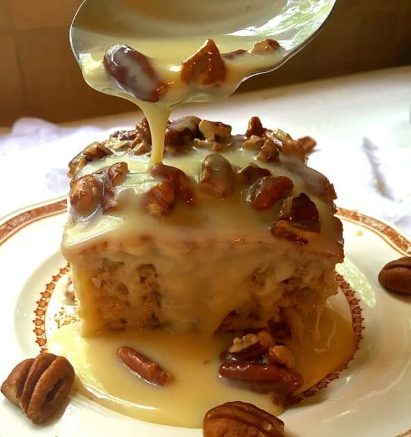 A piece of Southern Pecan Praline Cake with Pecan and Praline topping being drizzled over it