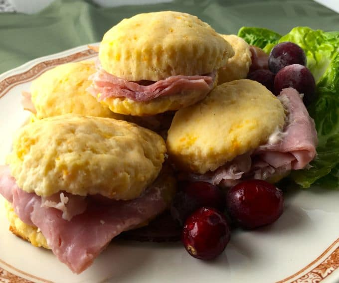 Plate filled with sweet potato biscuits with country ham garnished with cranberries and lettuce.