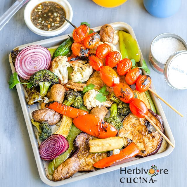 A sheet pan full of an assortment of grilled vegetables and two skewers with cherry tomatoes.