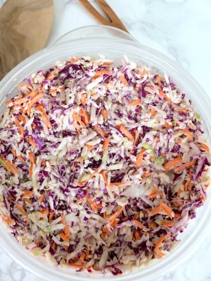 A plastic bowl full of coleslaw made with red and green cabbage and carrots.