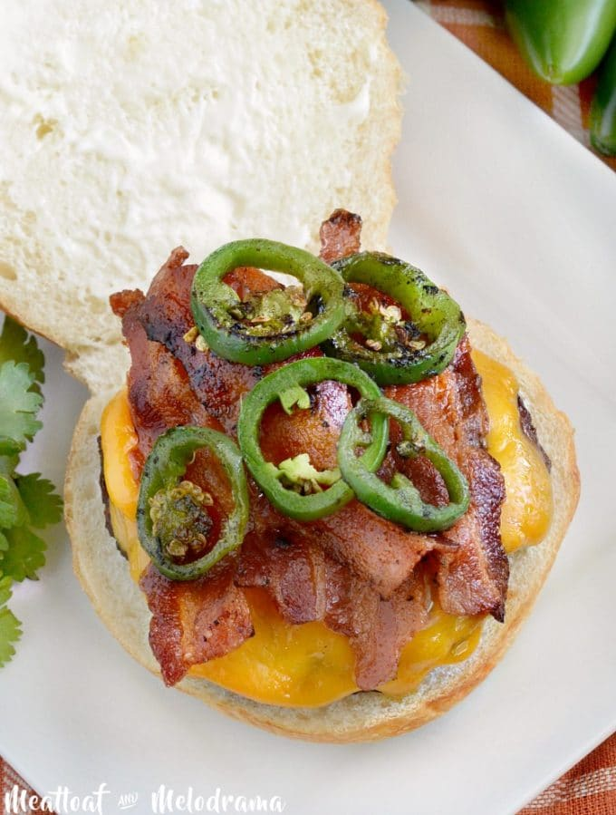 A hamburger on a bun topped with jalapeno slices, cheese and bacon.