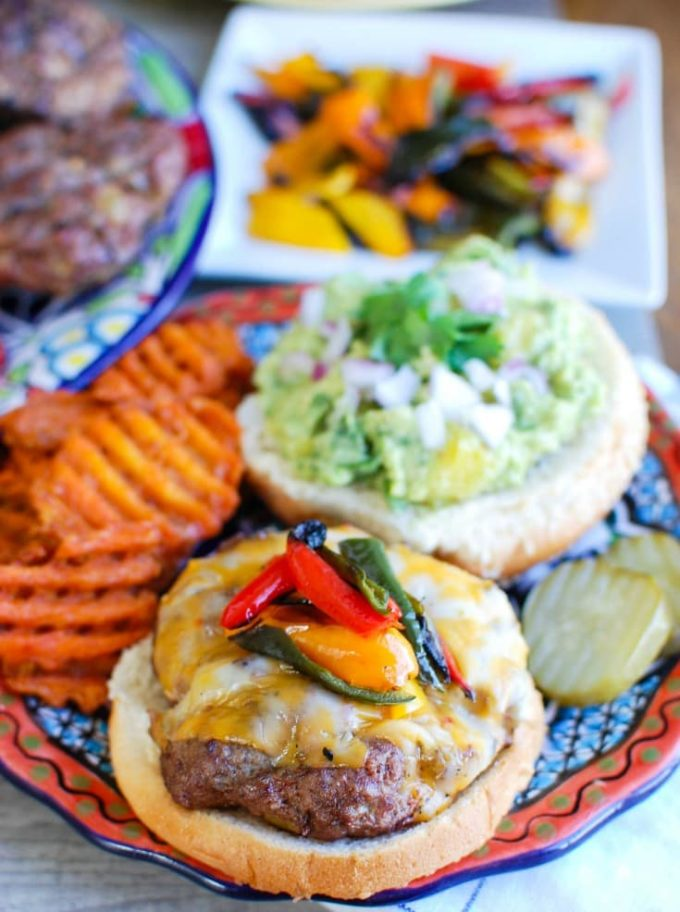 A hamburger on a bun topped with guacamole and peppers.