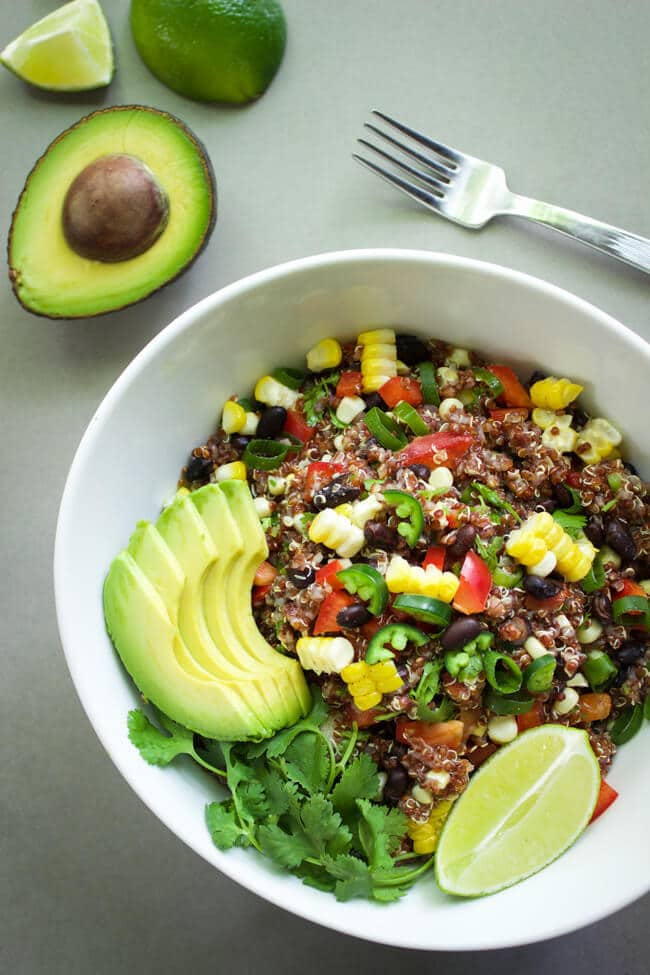 A white bowl full of quinoa salad and topped with avocado slices and a lime slice.