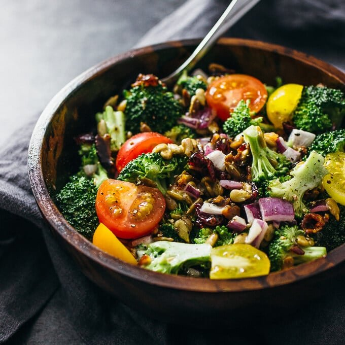 A wooden bowl of broccoli salad with tomatoes and red onions.