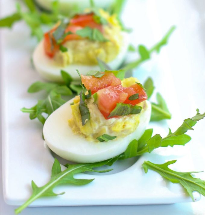 Two deviled eggs on arugula leaves topped with cut up tomatoes.