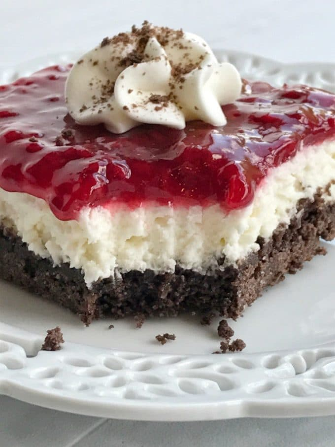 A three layer dessert with a chocolate crust, cheesecake filling and topped with raspberry sauce.