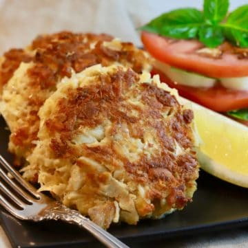 Three crab cakes on a black plate with a fork, sliced tomatoes and a slice of lemon.