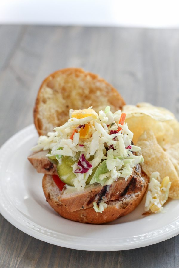A grilled pork tenderloin sandwich topped with slaw on a white plate.
