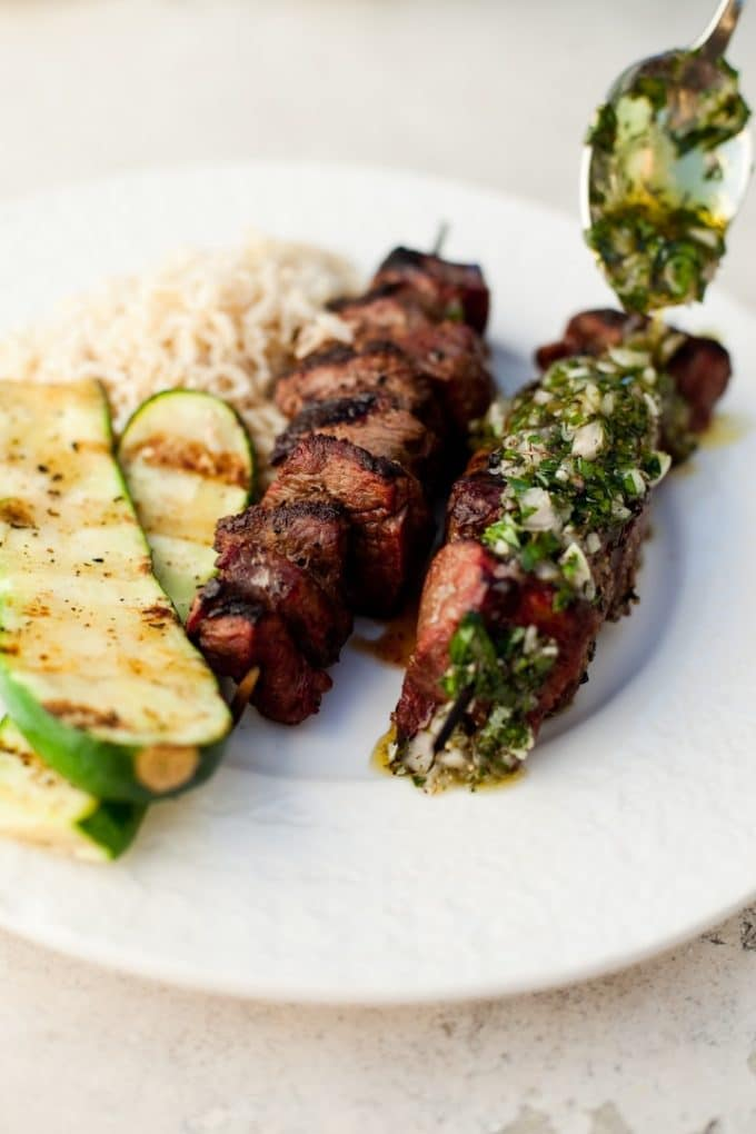 Two beef kabobs on a white plate with rice and grilled zucchini.