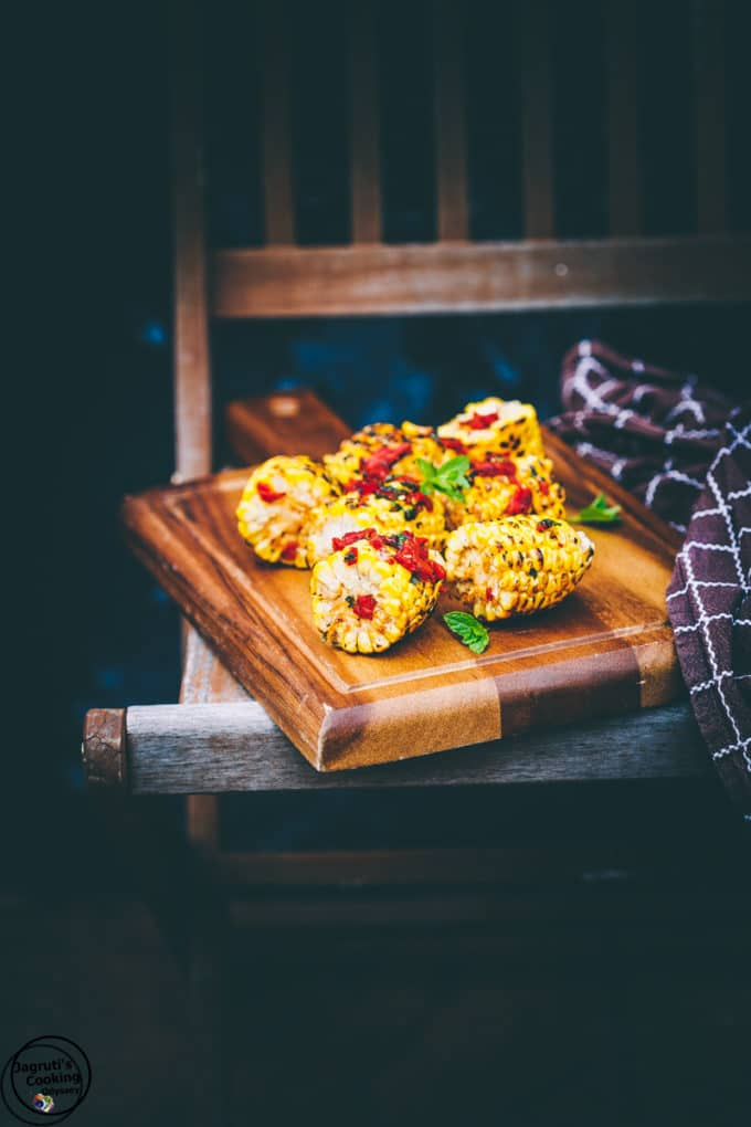 A wooden cutting board topped with grilled corn on the cob, topped with red pepper and basil.