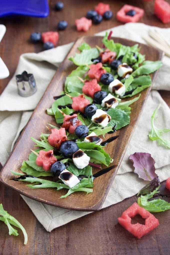 A wooden platter with red, white and blue skewers made with watermelon, blueberries and mozzarella cheese. A great 4th of July recipe.
