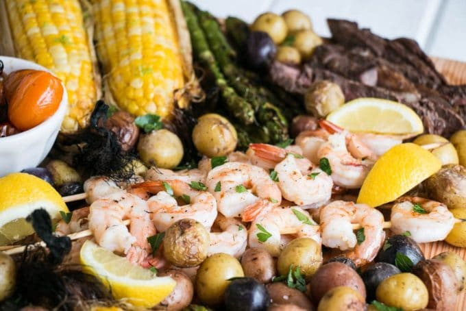 A serving board full of shrimp, baby potatoes, corn on the cob, and asparagus.