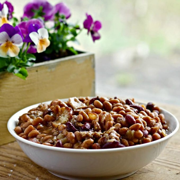 A white bowl full of baked beans with hamburger meat. A box of pansies is in the background.