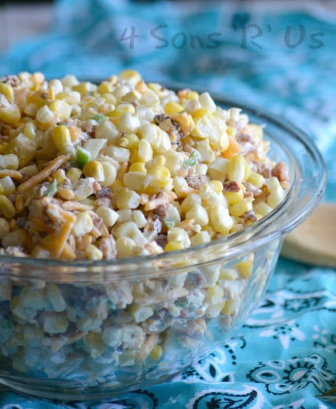 A clear glass bowl full of corn salad.
