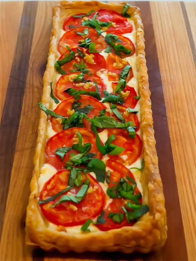 A large rectangle tomato tart on puff pastry, garnished with basil.