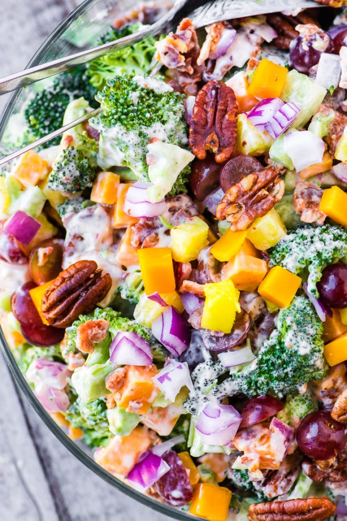 Broccoli salad in a clear glass bowl topped with pecans and pineapple chunks.