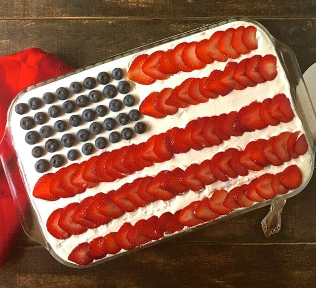 Red White and Blue No-Bake Icebox Cake with blueberries for the starrs and sliced strawberries for the stripes.