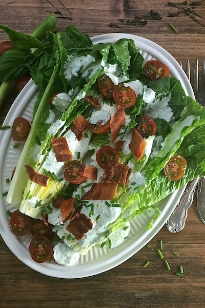 A new twist on an old classic, Romaine Wedge Salad with Green Goddess Dressing includes romaine lettuce, tasty green goddess dressing, bacon and cherry tomatoes.