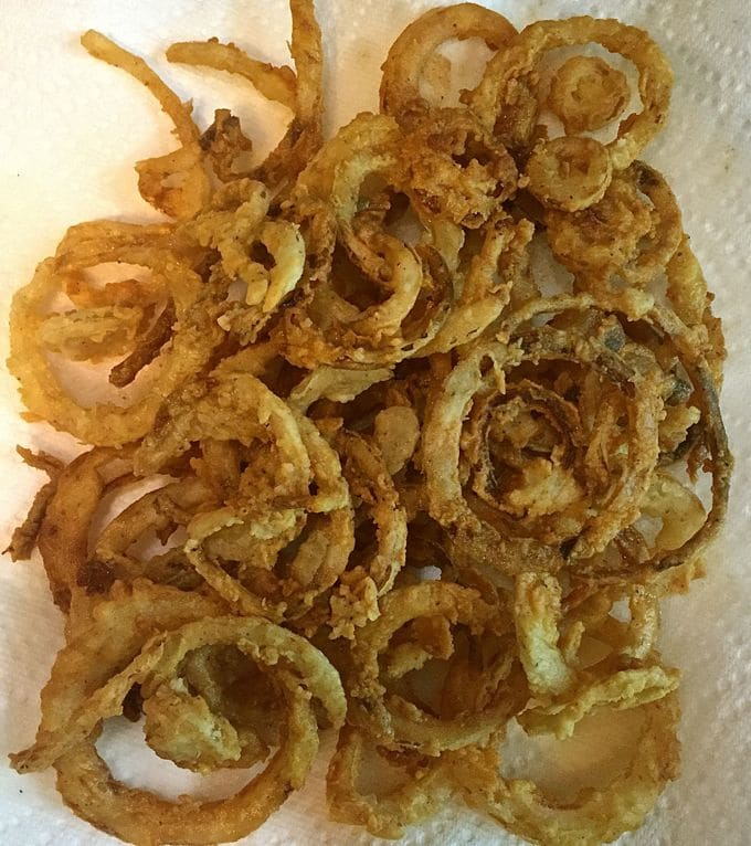 Southern Style Crispy Onion Rings sitting on paper towels to drain after cooking.