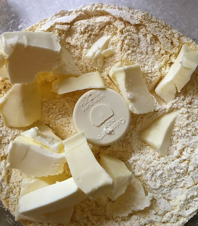 Adding butter to biscuit mix for Tomato Cobbler with Cornbread-Cheddar Biscuits