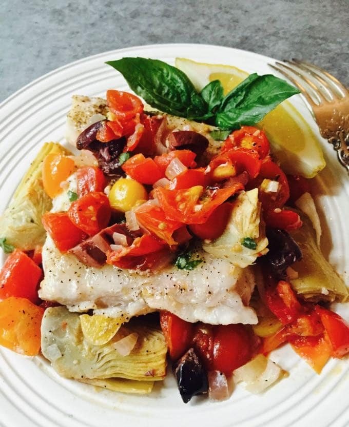 Tasty Baked Grouper with Tomatoes and Artichokes on a white plate, garnished with fresh basil.