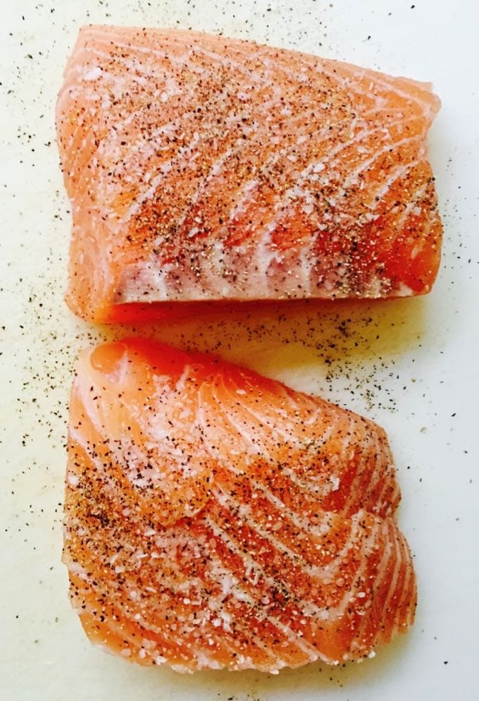Easy Pan Seared Salmon with Asparagus seasoning the fillets