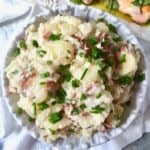 A large bowl of rustic mashed potatoes garnished with fresh chives.