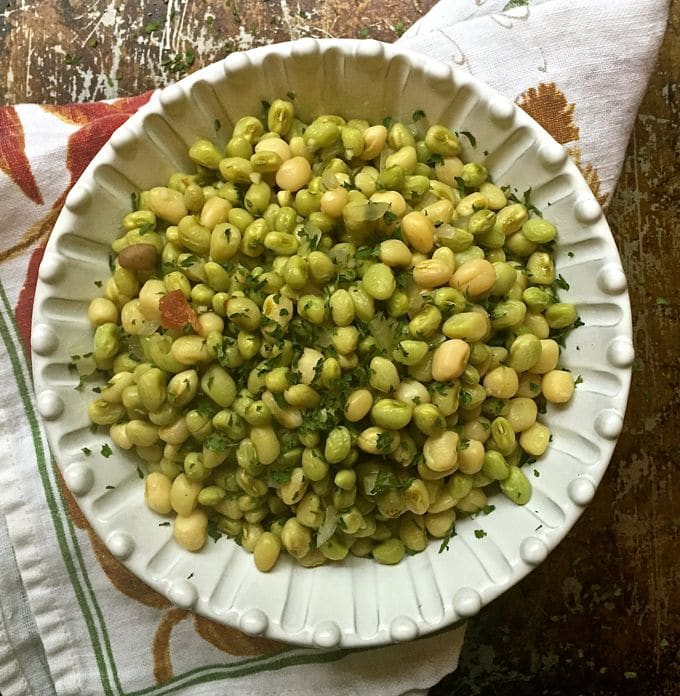 A white bowl full of peas resting on a kitchen towel.