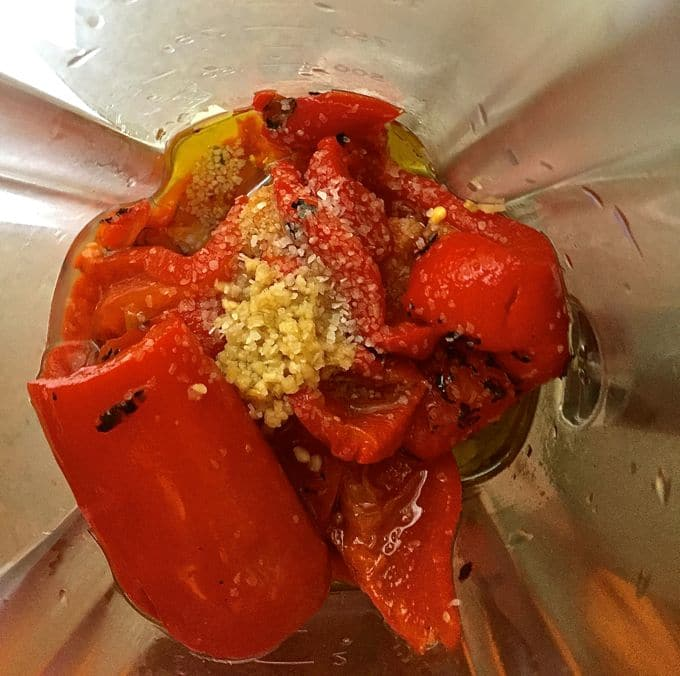 Roasted red peppers and other ingredients in a blender ready to process.