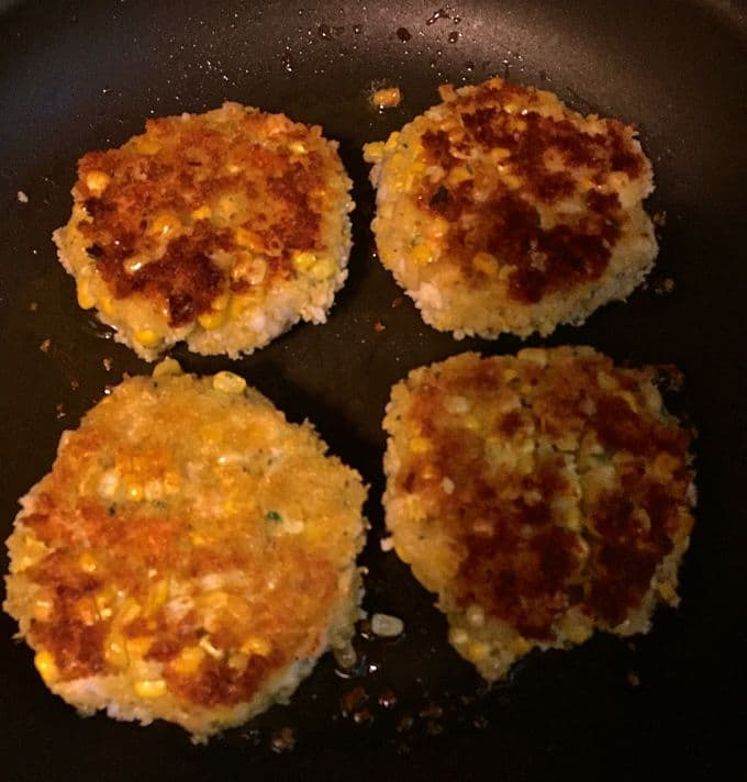 Four shrimp and corn fritters cooking in a skillet.