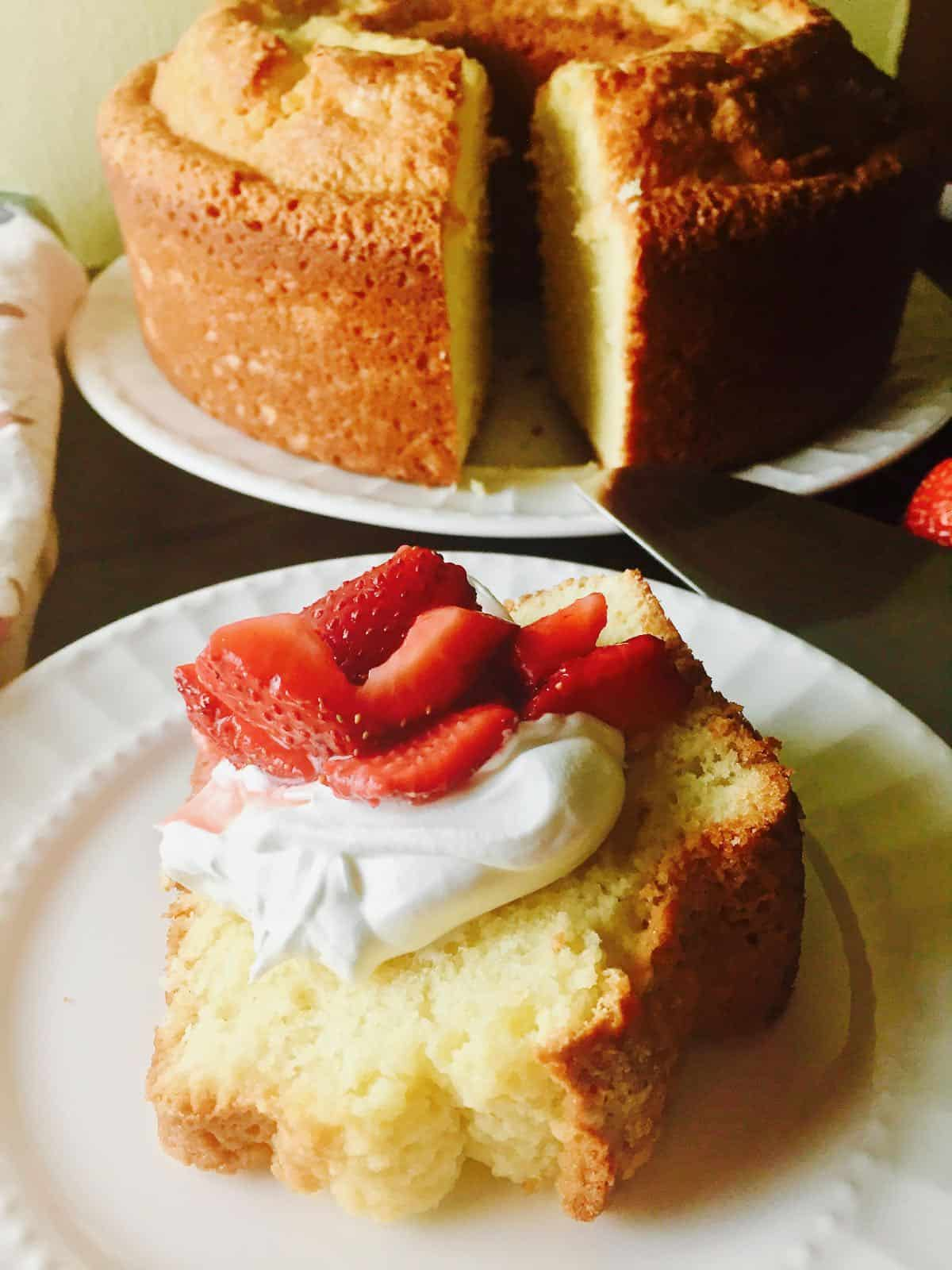 A large pound cake in the background with a slice cut out. The slice is topped with whipped cream and sliced strawberries.