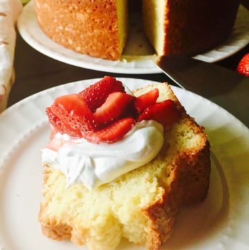 A slice of old-fashioned sour cream pound cake topped with whipped cream and sliced strawberries.