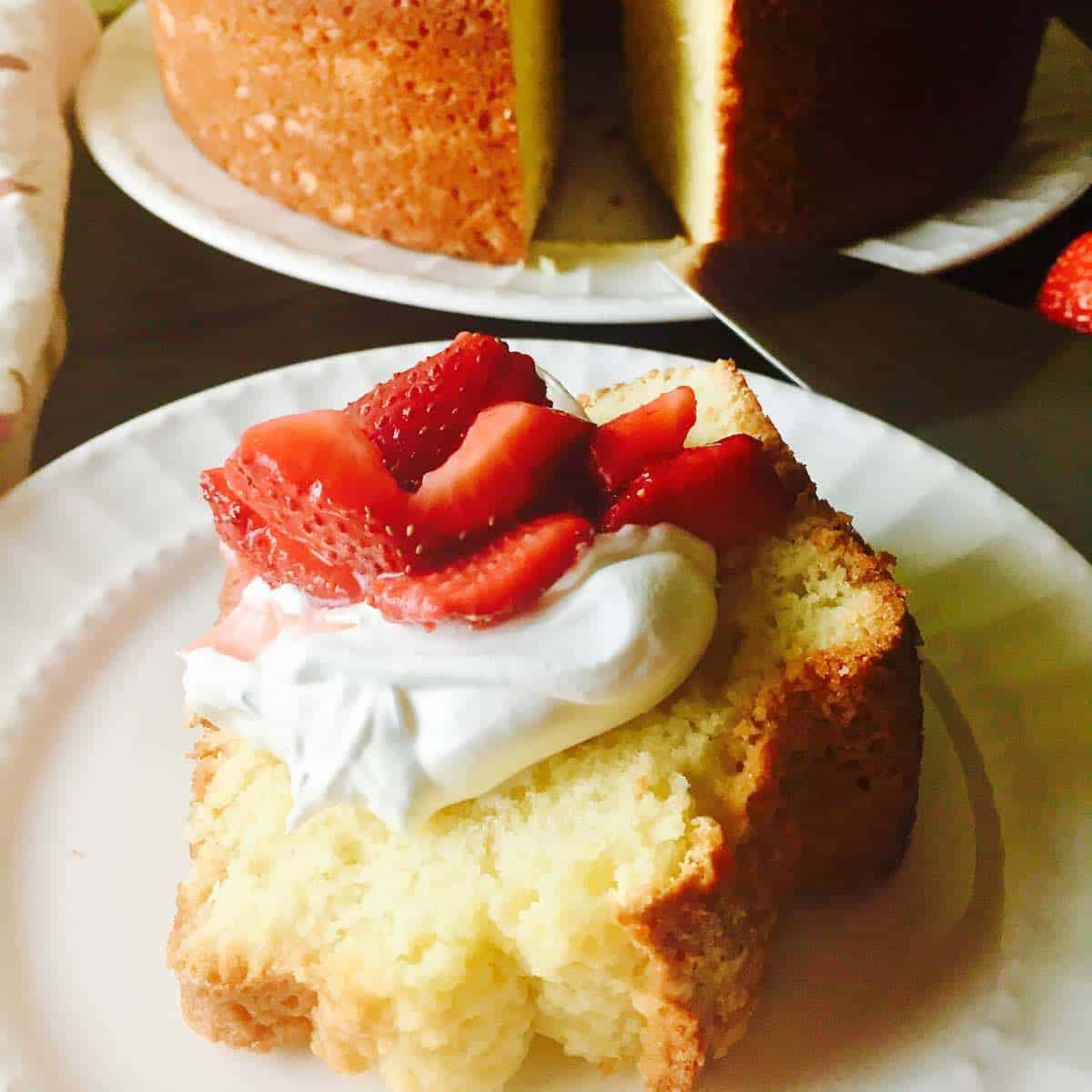 A slice of pound cake topped with whipped cream and sliced strawberries.