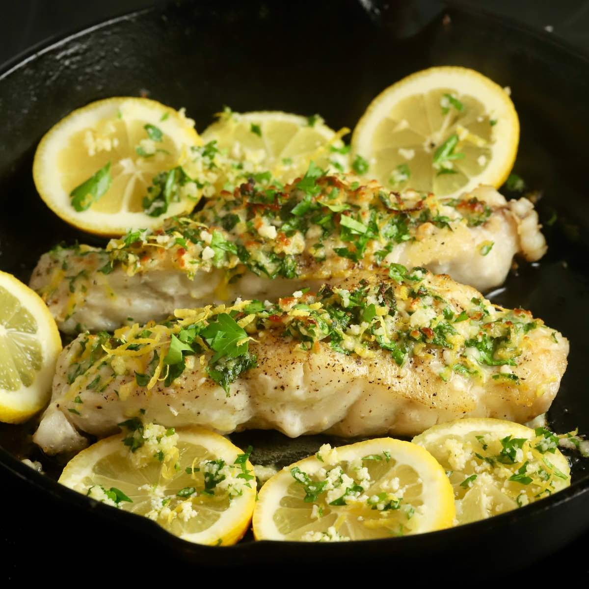 Easy Pan Seared Grouper with Gremolata in a skillet topped with lemon.