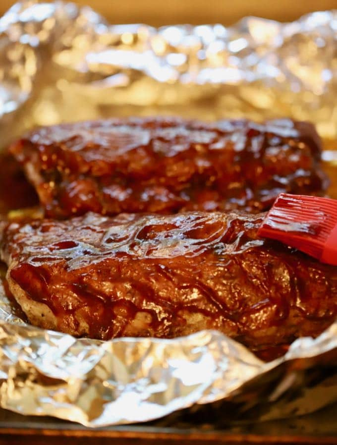 Adding BBQ sauce to Best Oven Baked Baby Back Ribs which have been wrapped in foil
