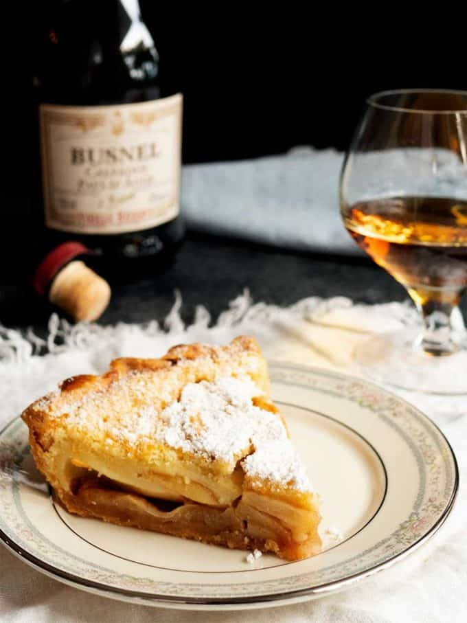 A slice of apple tart on a white plate with a glass of wine in the background.