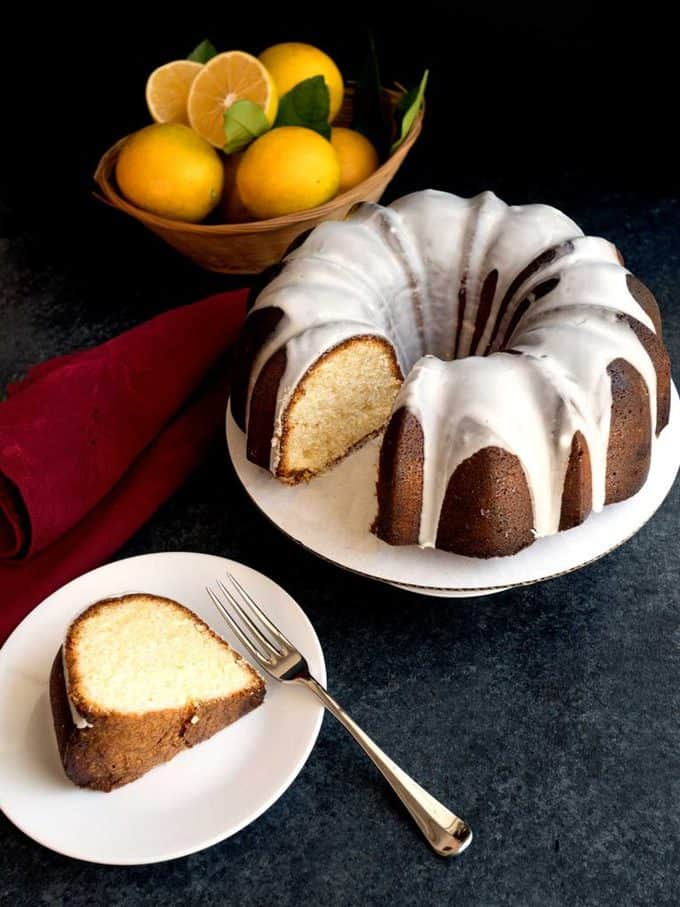 A lemon bundt cake with lemon glaze with lemons in the background.