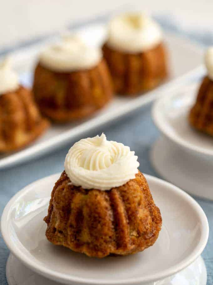 Mini bundt cakes topped with icing on a white plate.
