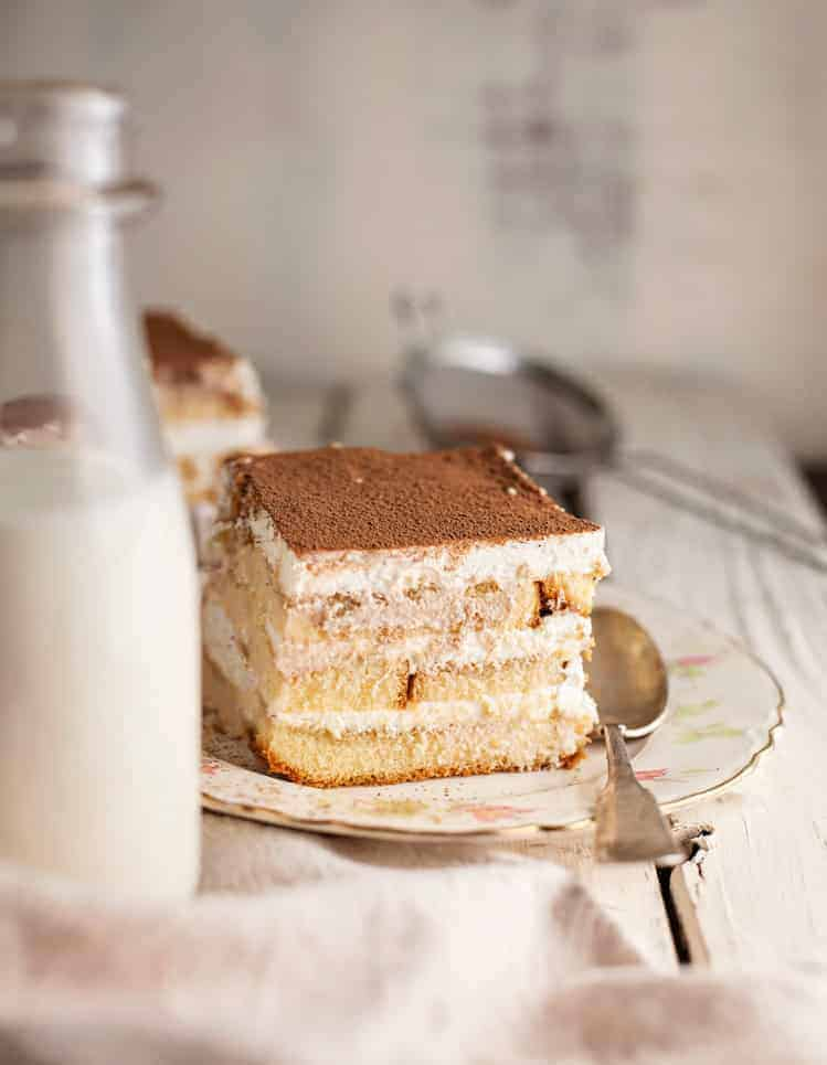 A piece of tiramisu cake on a plate with a bottle of milk.
