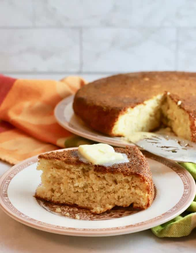A slice of cornbread topped with melted butter.