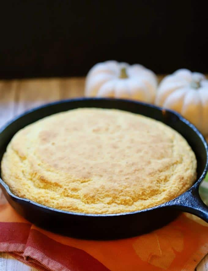 A skillet of cornbread hot out of the oven on a dish towel.