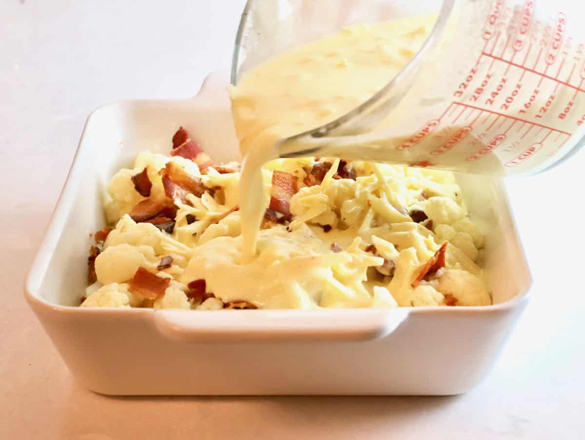 Pouring cheese sauce over cauliflower in a baking dish.