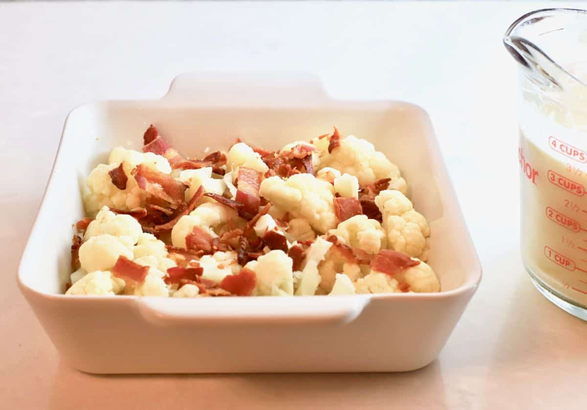 Cauliflower in a baking dish topped with bacon.