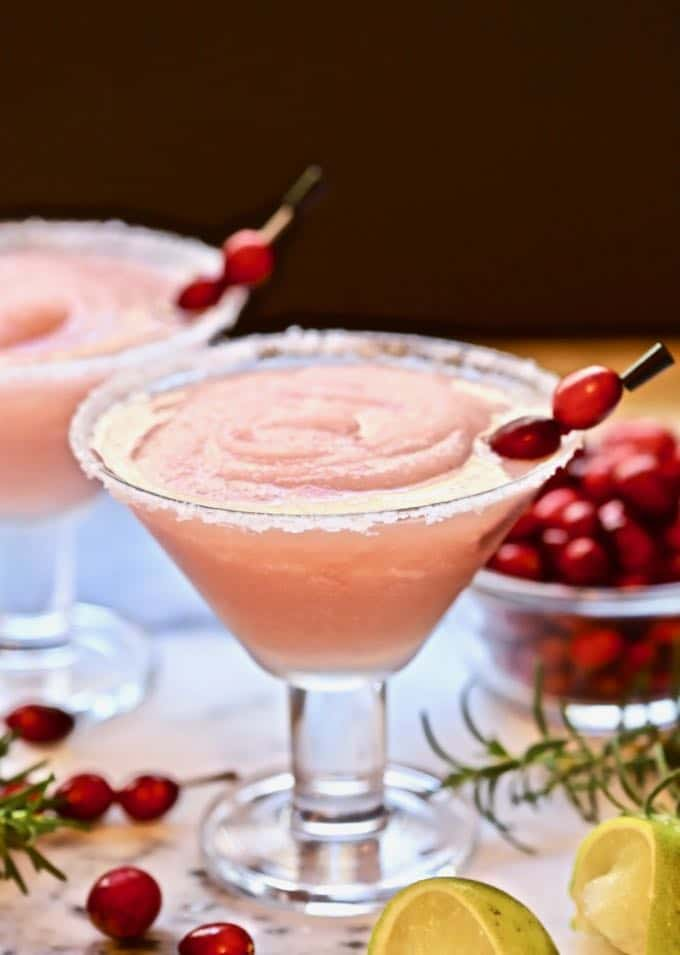 A frozen cranberry margarita with rosemary and fresh cranberries for garnish.