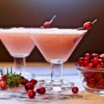 Two frozen Christmas margaritas garnished with fresh cranberries.