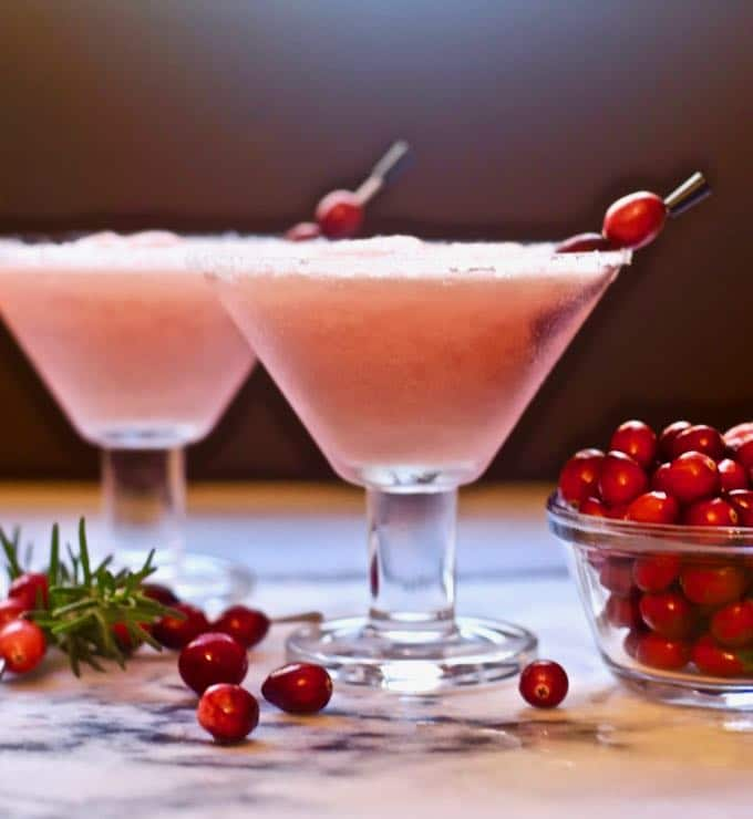 Two cranberry margaritas garnished with fresh cranberries.