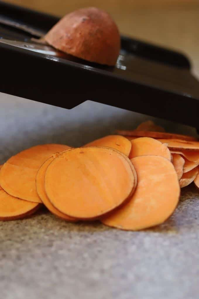 Using a mandoline to slice sweet potatoes for Healthy Roasted Sweet Potato Stacks