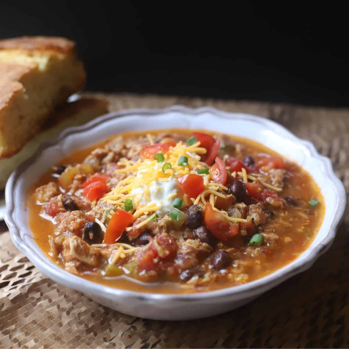 Hearty Chicken Chili with a Twist in a white bowl ready to serve with a side of cornbread